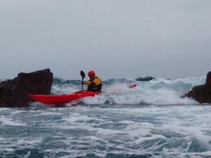 Jef en combinaison sèche lors d'une séance de saute-cailloux en kayak de mer.
