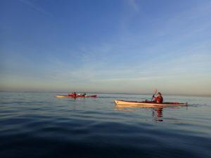 En kayak, sur une mer lisse comme un miroir
